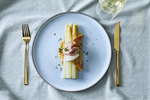 Gekookte witte asperges, geserveerd in omelet met ham